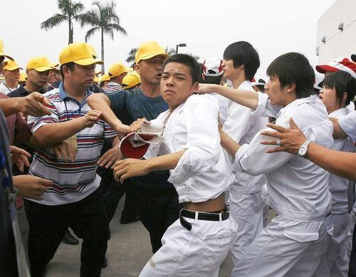 Travailleurs et travailleuses de Honda de Sihsan faisant face aux responsablesen syndicat unique officiel, avec des casquettes jaunes... de bon aloi.