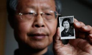 Zhang Hongbing avec dans la main une photo de sa mère