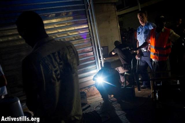 Police forçant l'entrée d'un commerce d'un  demandeur d'asile à Tel-Aviv