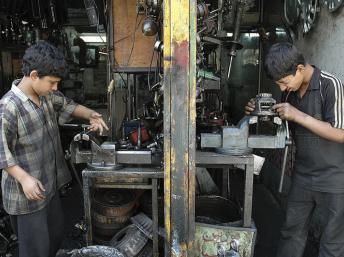 Des enfants dans un ateler de mécanique à Téhéran