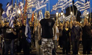 Man in camo trousers stands to attention in front of sea of Greek flag-wavers