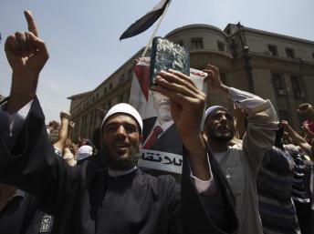 Un militant des Frères brandit le Coran devant le Palais de justice où seront jugés, le 25 août, six leaders des Frères musulmans.