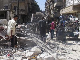 Des civils syriens dans les ruines d'un bâtiment détruit par un bombardement à Alep, le 9 septembre dernier. REUTERS/Abdalghne Karoof