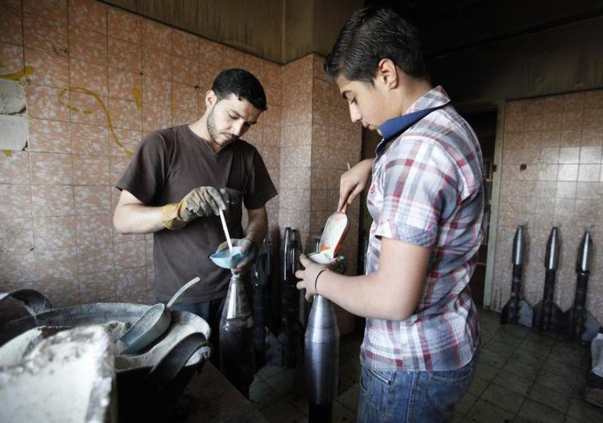 Des soldats de l'ASL préparant des obus de mortier, dans un atelier d'Alep, le 9 septembre. Photo Loubna Mrie. Reuters