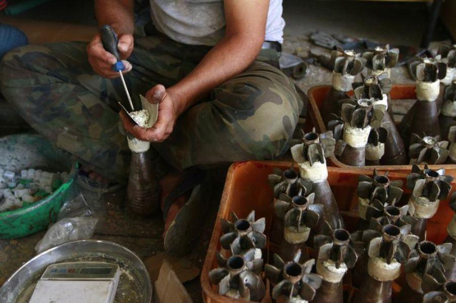 Un soldat de l'Armée syrienne libre remplit d'explosif des obus de mortiers dans une usine improvisée à Alep, le 4 septembre 2013. Photo Hamid Khatib. Reuters