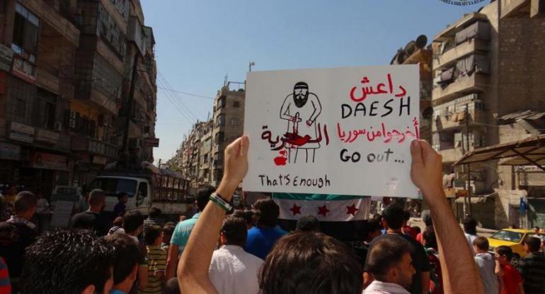 Manifestant brandissant une pancarte exigeant le départ de EIIL (Daesh en arabe) de Syrie