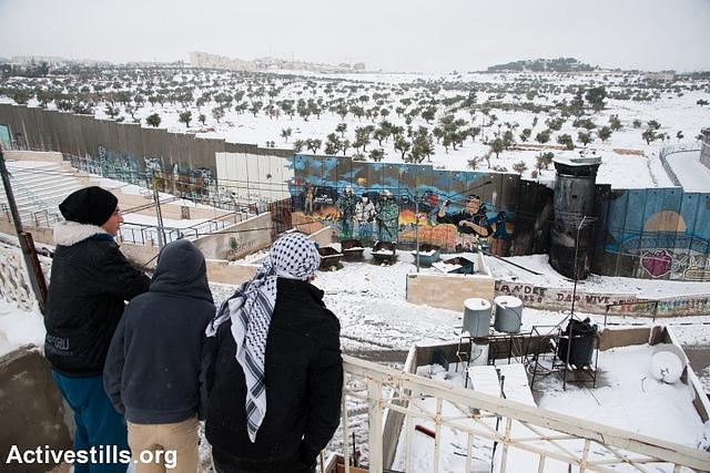 Des jeunes Palestiniens regardent le mur depuis le camp de réfugiés de Aida
