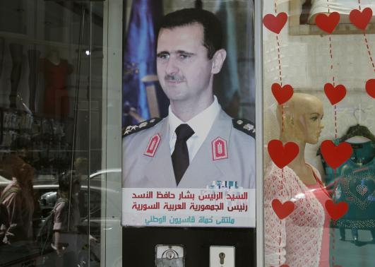 A picture of Syrian President Bashar al-Assad is seen at a shop in Damascus