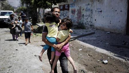 Un Palestinien tenant deux enfants dans ses bras, dans un quartier bombardé de Gaza, le 20 juillet 2014