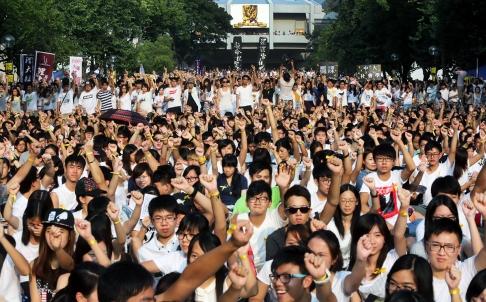 Le poing levé, en tee-shirts blancs (couleur du deuil), des milliers d'étudiants de l'Université de Hong Kong manifestent le 23 septembre