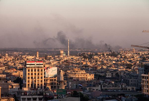 Centre de Damas, avec, une fois de plus, Assad en bandeau géant, et la fumée dans le quartier de Jobar
