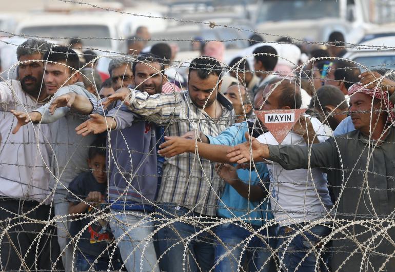 Des réfugiés kurdes en Syrie attendent de l'eau distribuée par le Croissant-Rouge turc...