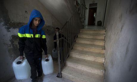 A Shuafat, un quartier de Jérusalem-Est, un jeune porte de l'eau dans sa maison, car il est prisonnier d'un «legal no man's land»:  les services israéliens ne s'en occupent pas. (The Guardian,  14 avril 2014)