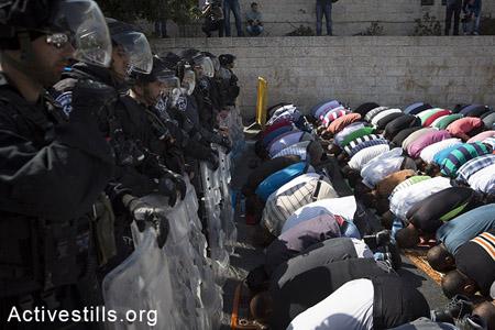 Des policiers israéliens, le 17 octobre 2014, bloquent l'accès à Al-Aqsa à des fidèles musulmans faisant leurs prières du vendredi, dans le quartier de Wadi Joz de Jérusalem-Est.