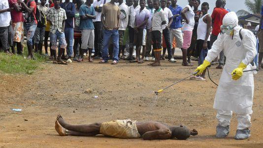 Un homme suspecté de souffrir d'Ebola est désinfecté par un soignant