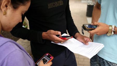 Trois jeunes utilisent leur téléphone mobile à Cuba  (22 décembre 2014)