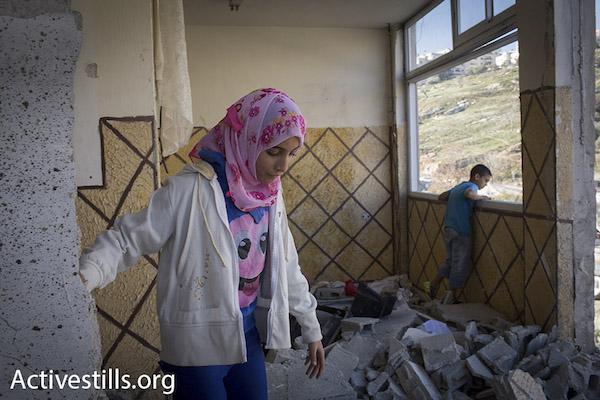 Membres de la famille d'Abed al-Rahman Shaloudi, qui tua deux personnes, y compris un bébé, se tiennent dans leur appartement, démoli par les autorités israéliennes dans le cadre d'un retour des destructions punitives de maison. Silwan, Jérusalem-Est, 19 novembre 2014.
