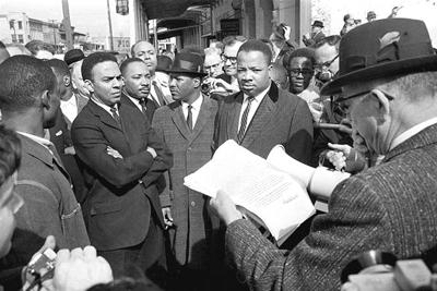 Au pont Edmund Pettus le 9 mars 1965, un maréchal fédéral lit une injonction à Andrew Young (bras croisés), le Dr Martin Luther King Jr., et d'autres marcheurs