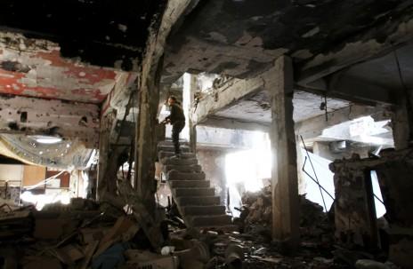 Un homme se tient dans les escaliers d'un immeuble en ruine, le 6 avril 2015, dans le camp de Yarmouk, à Damas, Syrie (YOUSSEF KARWASHAN/AFP)