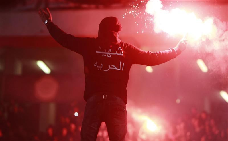 An Al-Ahly fan lights flares as he shouts slogans against the military council and police before their Egypt Premier League soccer match against Misr El-Makasa in Cairo Stadium