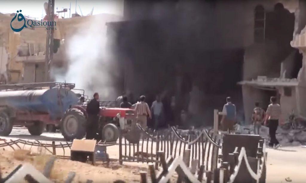 Des Syriens rassemblés autour des décombres d'un bâtiment suite à une frappe aérienne russe dans le village de Dair al-Asafeer.