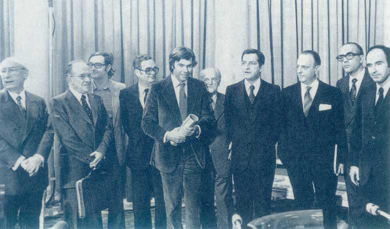 La signature du Pacte de la Moncloa (Palais) en octobre 1977. Outre, les franquistes recyclés (UCD), on y voit Felipe Gonzales, fringant au centre, Carillo et sa serviette, sur «sa gauche», avec Galvan à ses côtés (gauche), distrait. Adolfo Suarez regarde Felippe Gonzales et Manuel Fraga est intéressé par ce «nouvel homme» au costume de velours côtelé. Leopoldo Calvo Sottelo, à droite de Fraga, a le regard fixe, avec ses lunettes pesantes. Il est l'homme des chemins de fer (RENFE), de l'industrie chimique et acteur de la transition. Lepoldo Calvo Sottelo fut ministre du commerce sous Carlos Arias Navarro...