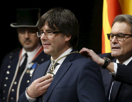 New Catalan President Puigdemont receives a medal from outgoing Catalan President Mas during Puigdemont's swearing-in ceremony as President of the Generalitat de Catalunya at Palau de la Generalitat in Barcelona