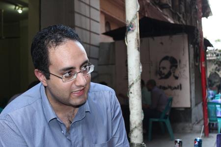 Moheb Doss en 2014. A l'arrière-plan, on voit un tag «Libérez Boudy» avec un portrait de ce jeune révolutionnaire emprisonné. (Photo de Hany Hanna)