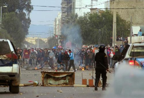"""A Kasserine, le 21 janvier 2016: la police affronte les jeunesse. Le Premier ministre exige la «patience» et n'annonce aucune mesure contre le chômage. Selon l'AFP, Inès Bel Aiba: «Le ministre Kamel Jendoubi (société civile et droits de l'Homme) a, lui, affirmé que le chef du gouvernement ne tarderait pas à annoncer des mesures pour """"la jeunesse, l'emploi et la prise en charge des situations difficiles». Interrogé par l'AFP, l'analyste Selim Kharrat ne s'est pas montré «étonné» de l'absence d'annonces immédiates. «Si le gouvernement avait des solutions à proposer, il l'aurait fait bien avant l'éclatement de cette crise. Il ne faut pas oublier que sa marge de manœuvre est très réduite»"""", notamment financièrement, a-t-il dit. Mais il """"aurait pu prendre des mesures non coûteuses"""" contre la corruption et a """"manqué une occasion de donner un signal positif"""", a ajouté M. Kharrat. Selon lui, «ce que réclament les manifestants, c'est non seulement du travail mais aussi des dirigeants intègres et au service des populations». La réponse du gouvernement, de facto, les ex-Benaliste et Ennhada: le couvre feu! (Réd. A l'Encontre)"""