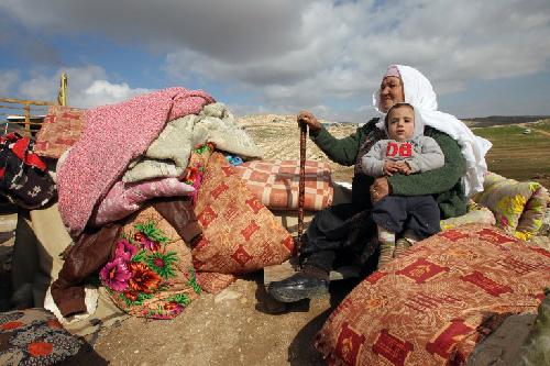 Une femme palestinienne assise avec un enfant à côté de ce qu'ils ont pu récupérer des restes de leur maison après qu'elle a été démolie par les bulldozers israéliens dans la zone militaire de Musafir Jenbach, qui comprend plusieurs villages, au sud de la ville cisjordanienne de Hébron, le 2 février 2016. In The Times of Israël du 4 février 2016. Il faut prouver, par l'image, «qu'il n'ont pas droit à la résidence».