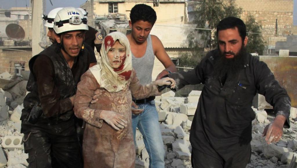 Des secouristes aident une jeune femme à fuir les bombardements, le 10 avril, au nord d'Alep. Le 13 avril «le régime organisait des élections»