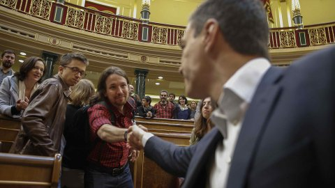 Pablo Iglesias sert la main à Pedro Sanchez. Derrière Iglesias, Íñigo Errejón