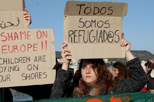 Une volontaire manifestant au port de Lesbos tient une pancarte: «Nous sommes tous des réfugiés»
