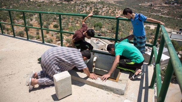 Des habitants en Cisjordanie contrôlent le réservoir d'eau de leur village; au bas, la colonie de Kiryat Netafim
