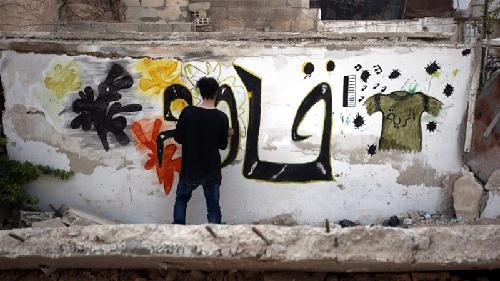 L'artiste syrien Noor écrit sur un mur d'un quartier périphérique de Damas: «Résister»