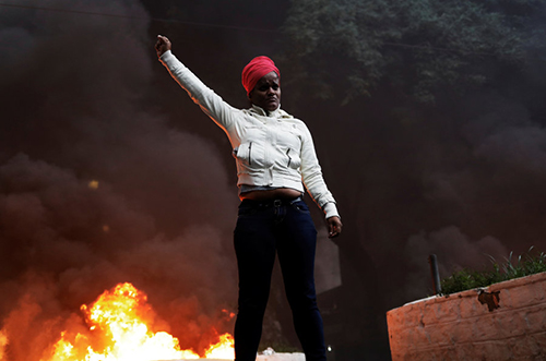 A member of Brazil's Movimento dos Sem-Teto (Roofless Movement) gestures in front of a burning barricade during a protest against President Temer's proposal reform of Brazil's social security system in the general strike in Sao Paulo