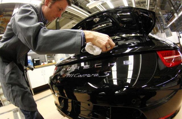 A worker cleans the new Porsche 911 sports car at the Porsche factory in Stuttgart-Zuffenhausen