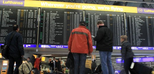 Passengers look at a flight departure information board at the main terminal of Frankfurt's airport