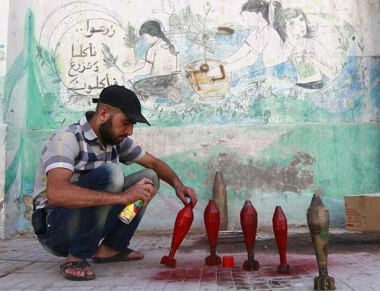 549752-a-free-syrian-army-fighter-spray-paints-on-improvised-mortar-shells-at-a-weapon-factory-in-aleppo