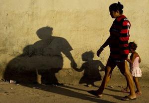 387847_une-bresilienne-marche-avec-sa-fille-dans-une-rue-d-une-favela-de-rio-de-janeiro-le-22-aout-2012