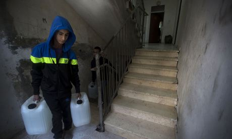A boy carries water to his house in Shuafat.