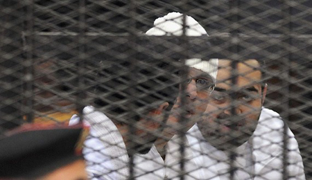 Political activists Ahmed Maher, Ahmed Douma and Mohamed Adel of 6 April movement look on from behind bars in Abdeen court in Cairo